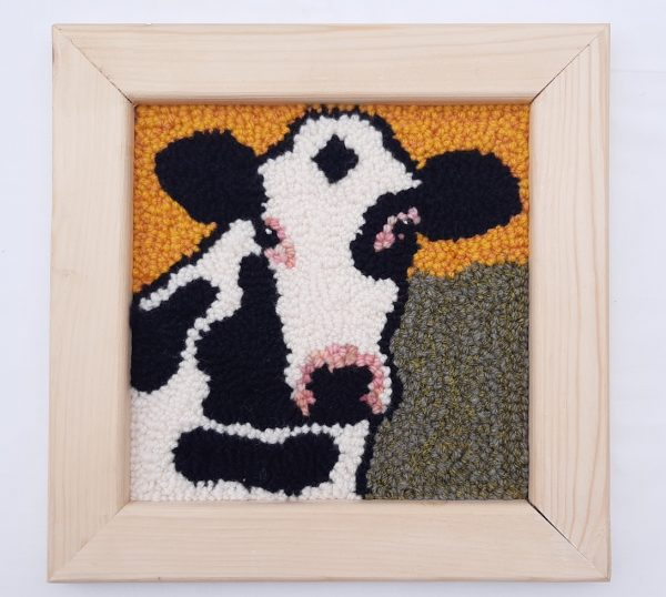 Framed punch needle pattern showing a cow