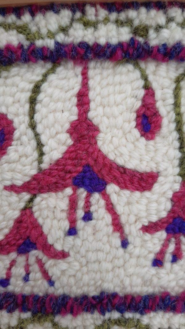 Close up view of punch needle pattern showing fushia flowers