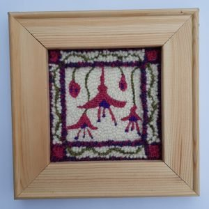 Framed punch needle pattern showing fushia flowers