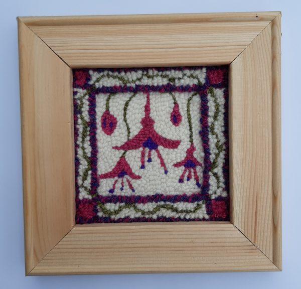 Framed punch needle pattern showing fushia flowers