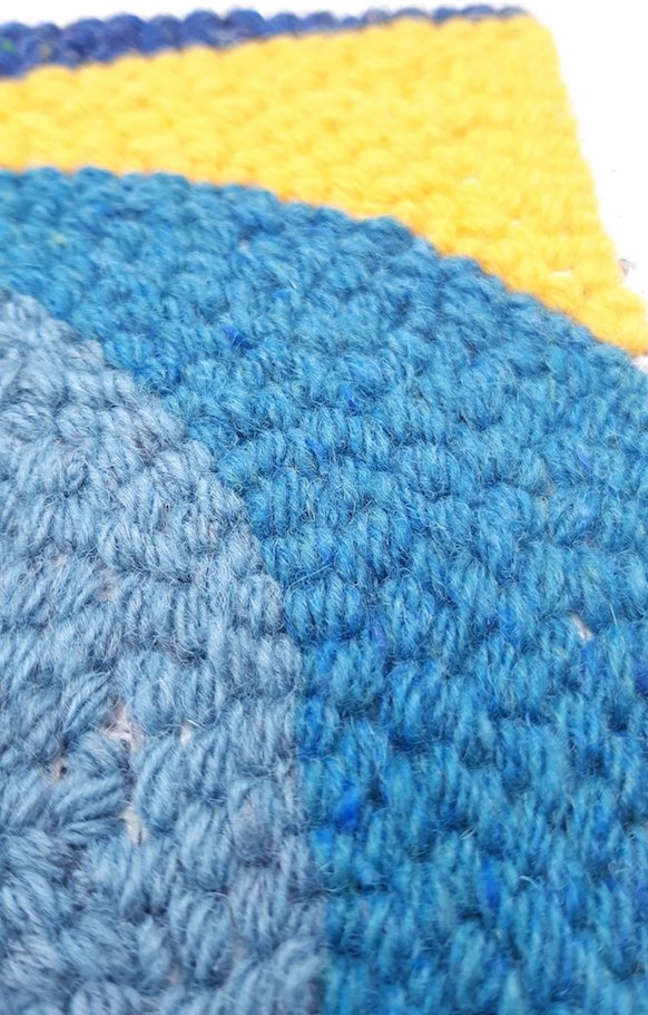Close up view of a punch needle pattern showing a blue lighthouse