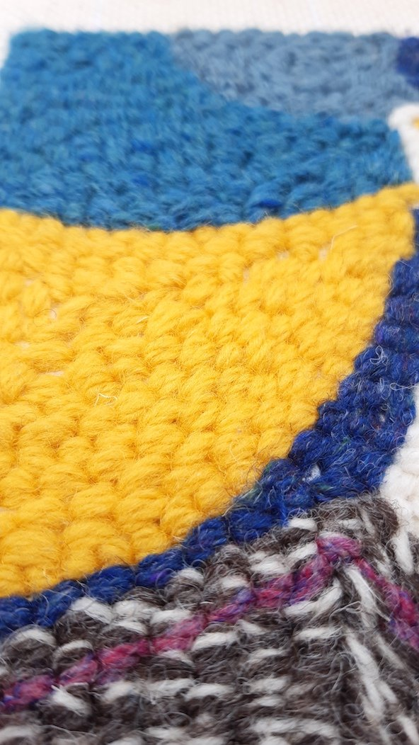 Close up view of a punch needle pattern showing a blue lighthouse and yellow light