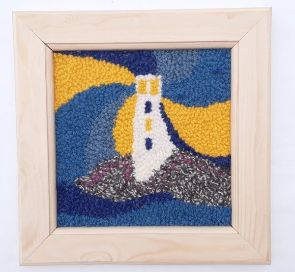 Framed punch needle pattern showing a blue lighthouse